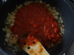 chopped tomatoes were added to onions on to a pan